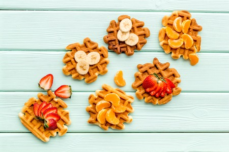 Homemade bakery. Breakfast with Belgian waffles with strawberry, tangerine and banana toppings on mint green wooden table background top view Фото со стока - 122768184