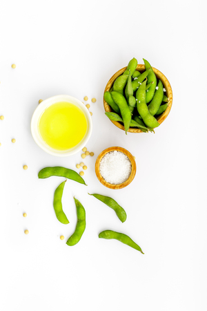 Ingredients. Green soybeans or edamame and oil for fresh healthy organic food on white background top view