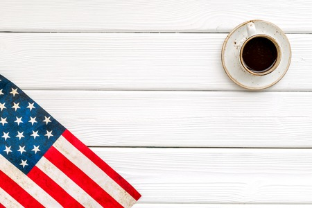 Symbol of Independence and Memorial day of United States of America with flag and cup of coffee on white wooden background top view mock up