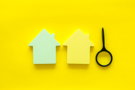 New house purchase. Property insurance concept with house toy and magnifier on yellow background top view Stock Photo