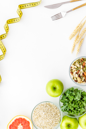 Maßband, Äpfel, Hafermehl und Grapefruit zum Abnehmen auf weißem Hintergrund Draufsichtmodell Standard-Bild