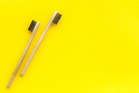 Dental care with eco friendly bamboo tooth brush on yellow background top view space for text