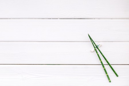 asian cuisine set with bamboo sticks for sushi and maki on white wooden background top view mock up 写真素材