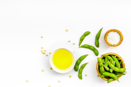 vegan food with green soybeans or edamame and oil on white background top view copy space