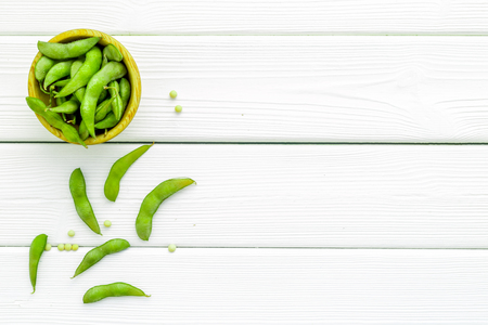 vegan food with green soybeans or edamame on white wooden background top view copy space