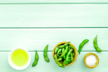 Fresh edamame and oil on mint green wooden background top view mock up Reklamní fotografie