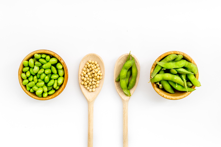 Vegan food concept with green soybeans or edamame in spoon and bowl on white desk background top view