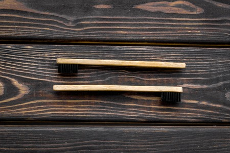 Zero waste lifestyle concept. Dental care with eco friendly bamboo tooth brush on wooden background top view