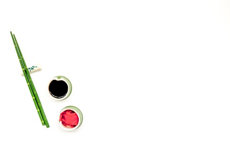 Oriental table set up. Japanese food cooking set with soy sauce, ginger, bamboo sticks for sushi or maki on white background top view copy space