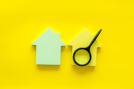 Property insurance concept. Buy house with house figure and magnifier on office desk yellow background top view Stock Photo