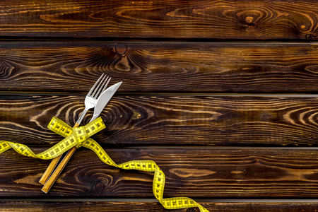 Medical starvation concept. Fork and knife near measuring tape on wooden background top view copy space 写真素材