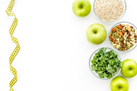 Proper nutrition. Medical starvation. Diet for weight loss concept with measuring tape, greenery and oat on white background top view copy space