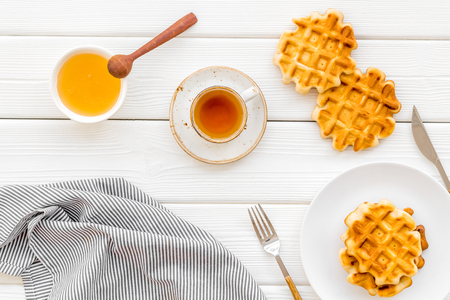 Sweet breakfast. Homemade Viennese waffles with honey and tea, flatware on white wooden background top view