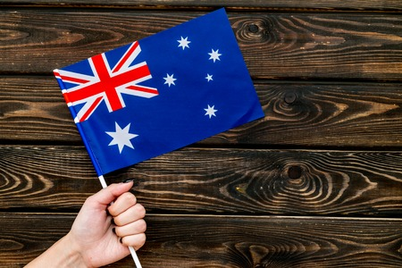 Flag of Australia in hand on wooden background top view.