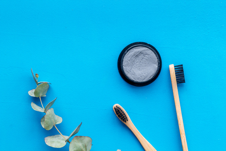 Dental care. Eco materials concept with bamboo tooth brush, toothpaste with bamboo carbon and plant on blue background top view Stock Photo