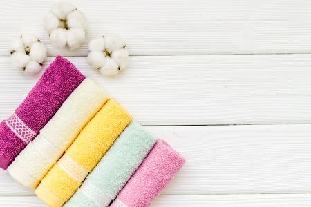 Prodotti in cotone di alta qualità. Accessori da bagno in cotone con asciugamani su sfondo bianco in legno vista dall'alto mockup Archivio Fotografico