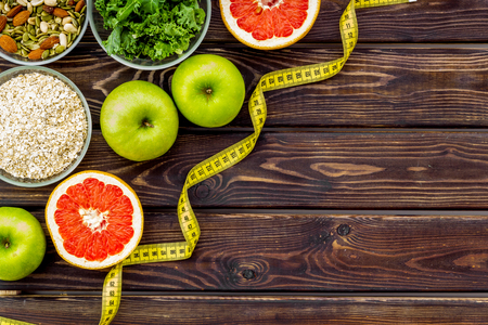 Proper nutrition. Medical starvation. Diet for weight loss concept with measuring tape, greenery and oat on wooden background top view copy space
