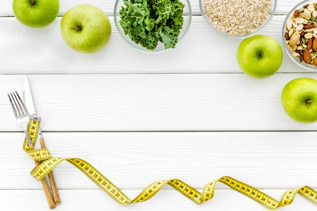 Proper nutrition. Medical starvation. Diet for weight loss concept with measuring tape, greenery and oat on white wooden background top view copy space