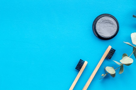 Dental care. Eco materials concept with bamboo tooth brush, toothpaste with bamboo carbon and plant on blue background top view copy space Stock Photo