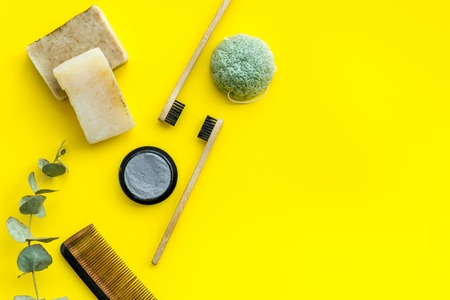 Zero waste lifestyle concept. Eco friendly materials for washing. Bamboo tooth brush, bamboo carbon toothpaste, comb, organic soap on yellow background top view space for text
