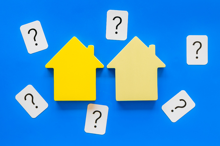 Purchasing a new property on credit. Mortgage credit concept with house toy and question mark on blue background top view Stock Photo