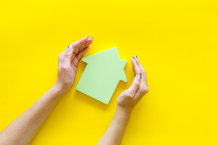 Search for a new house concept with house figure in hands on yellow office desk background top view. Stock Photo