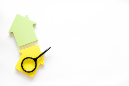 Purchasing a new property on credit. Mortgage credit concept with house toy and magnifier on white background top view copy space