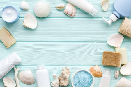 Homemade spa concept. Organic cosmetic frame with Dead Sea salt, cream and lotion on mint green wooden background top view mock up