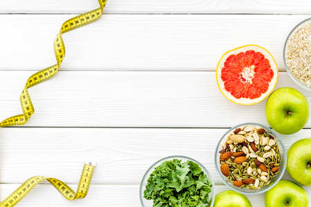 Proper nutrition. Medical starvation. Diet for weight loss concept with measuring tape, greenary and oat on white wooden background top view copy space Stok Fotoğraf