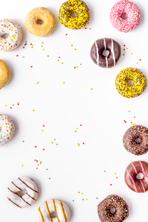 Sweet break or breakfast. Modern design with bright donuts frame on white background top view mock up
