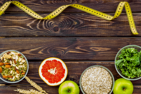 Proper nutrition. Medical starvation. Diet for weight loss concept with measuring tape, greenary and oat on wooden background top view copy space 写真素材