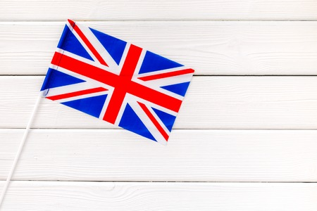 Symbol of the national day of United Kingdom of Great Britain concept with flag on white wooden background top view