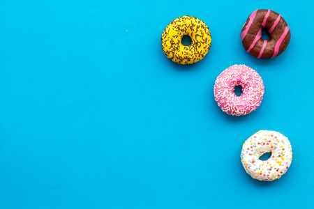 Modern pattern. Glazed decorated donuts for sweet break on blue background flat lay copy space