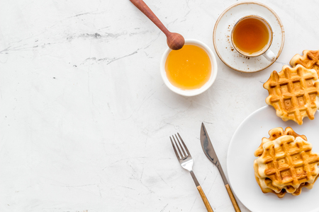 Sweet breakfast. Homemade Viennese waffles with honey and tea, flatware on marble background top view make-up