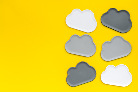 Share information on the Internet. Clouds figures for cloud storage on yellow office background top view mockup