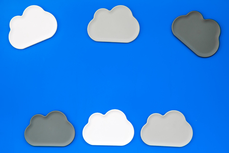 Share information on the Internet. Clouds figures for cloud storage on blue office background top view mockup Фото со стока