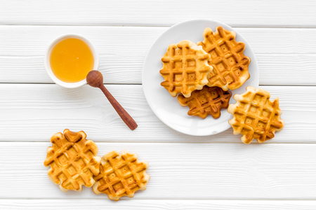 Sweet snack. Viennese waffles. Homemade Belgian waffles with honey on served table on white wooden background top view 写真素材