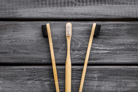 Dencal care. Eco materials concept with bamboo tooth brush on wooden background top view