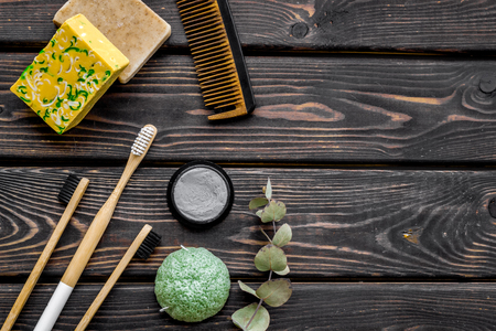 Zero waste lifestyle concept. Eco friendly materials for washing. Bamboo tooth brush, bamboo carbon toothpaste, comb, organic soap on wooden background top view space for text Фото со стока