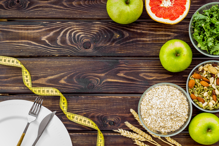 Proper nutrition. Medical starvation. Diet for weight loss concept with measuring tape, greenary and oat on wooden background top view copy space Фото со стока