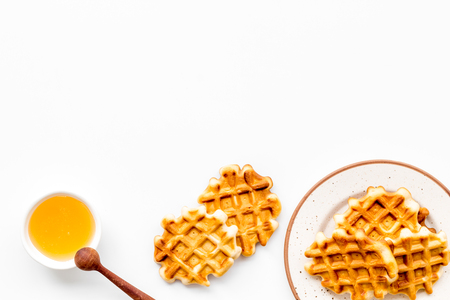 Sweet snack. Viennese waffles. Homemade Belgian waffles with honey on served table on white background top view space for text Фото со стока