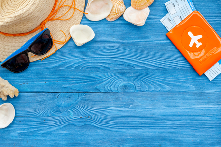 Turistic set. Planning vacation to the seaside with straw hat, sun glasses, shells, passport and tickets on blue background top view mock-up