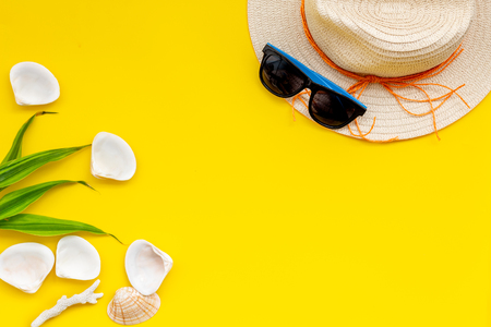 Planning vacation. Summer travaling to the sea with straw hat, sun glasses, shells on yellow background top view mock up