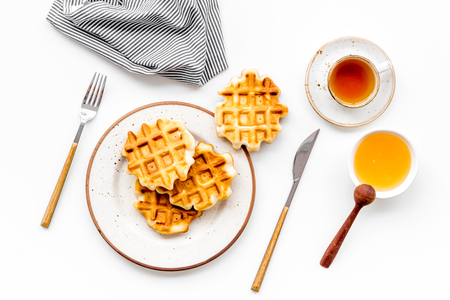Sweet breakfast. Homemade Viennese waffles with honey and tea, flatware on white background top view
