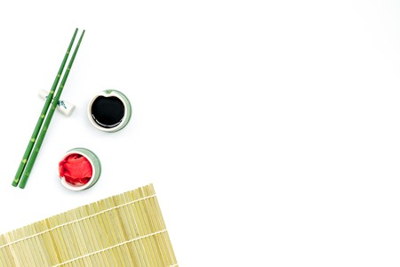 bamboo sticks, soy sauce, ginger for sushi and maki cooking on white table background top view mockup