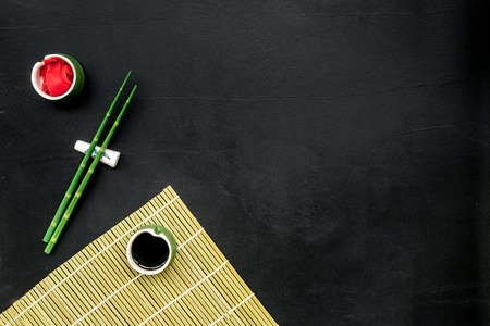 bamboo sticks, soy sauce, ginger for sushi and maki cooking on black table background top view mockup