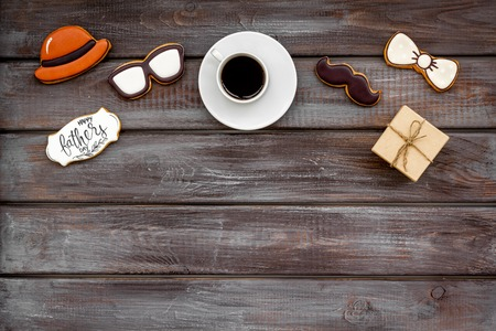 moustache, hat, glasses, cup of black coffee, box with gift and cookie with copy for Happy Father Day celebration party on wooden background top view copy space