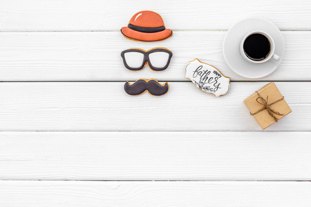 Happy Father Day celebration with hat, glasses, moustache cookies, gift and coffee on white wooden background top view mockup
