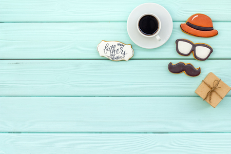 moustache, hat, glasses, cup of black coffee, box with gift and cookie with copy for Happy Father Day celebration party on mint green wooden background top view copy space