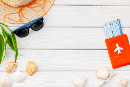 Planning vacation. Summer travaling to the sea with straw hat, sun glasses, shells and tickets and passport on white wooden background top view mock up
